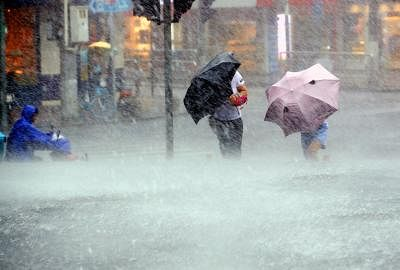 SHANGHAI, Aug. 10, 2019 (Xinhua) -- Pedestrians walk against heavy rain on Xinsong Road in Shanghai, east China, Aug. 10, 2019. The Shanghai central meteorological station updated the yellow alert for heavy rain to orange alert on Saturday afternoon, as Typhoon Lekima landed in east China