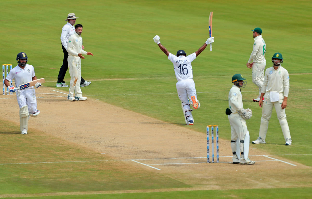 Mayank Agarwal raises his bat after scoring a hundred runs during the second day  of the first cricket test match against South Africa in Visakhapatnam.