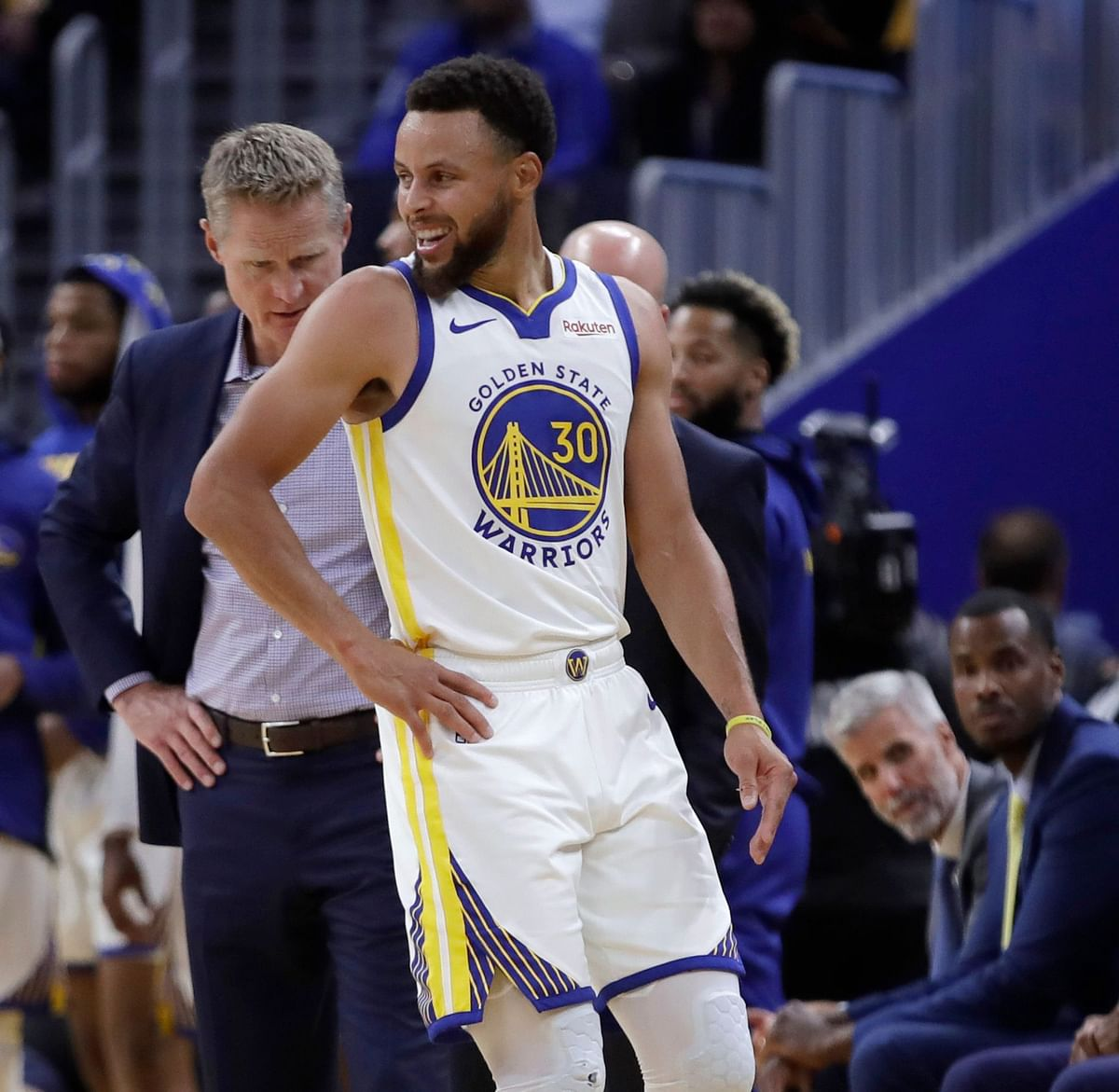 Golden State Warriors coach Steve Kerr, left, observes Stephen Curry (30) after Phoenix Suns' Aron Baynes fell on him during the second half of an NBA basketball game Wednesday, Oct. 30, 2019, in San Francisco. Curry left the game with injury.