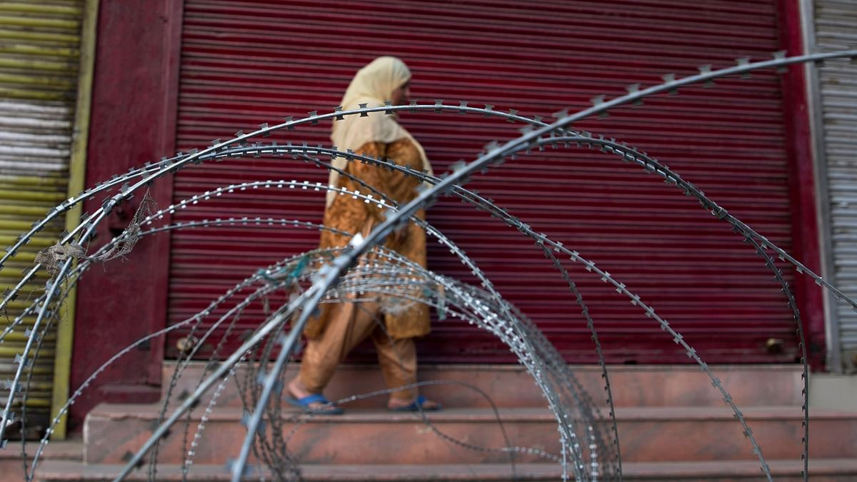 A Kashmiri woman walks past a barbed wire barricade set up by paramilitary soldiers during restrictions in Srinagar.