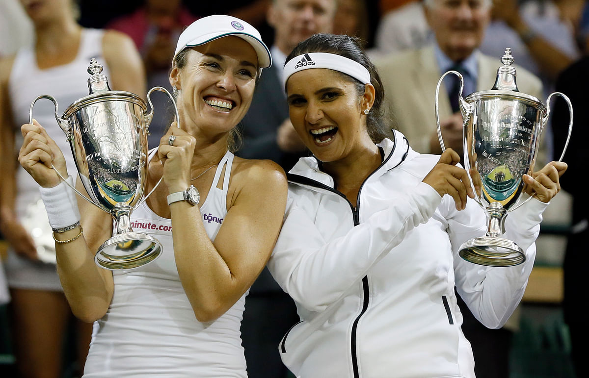Sania Mirza and Martina Hingis hold their trophies after winning the 2015 Wimbledon women's doubles final.