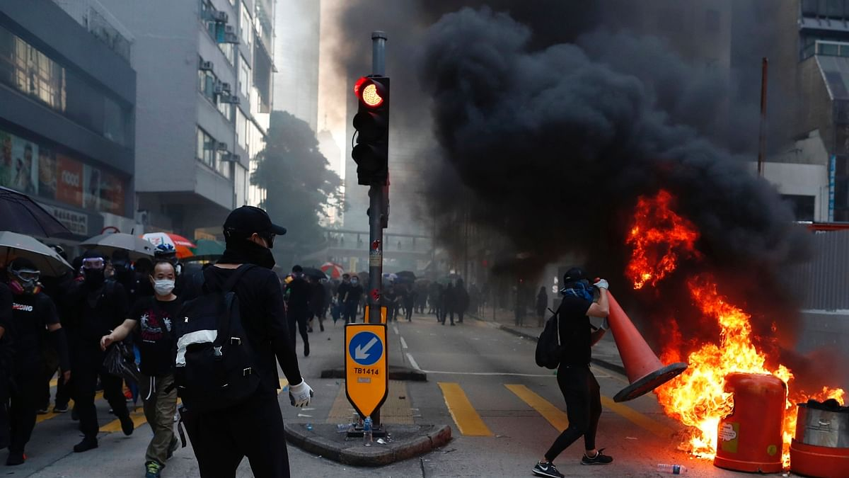 Anti-government protesters set fire to block traffic in Hong Kong.