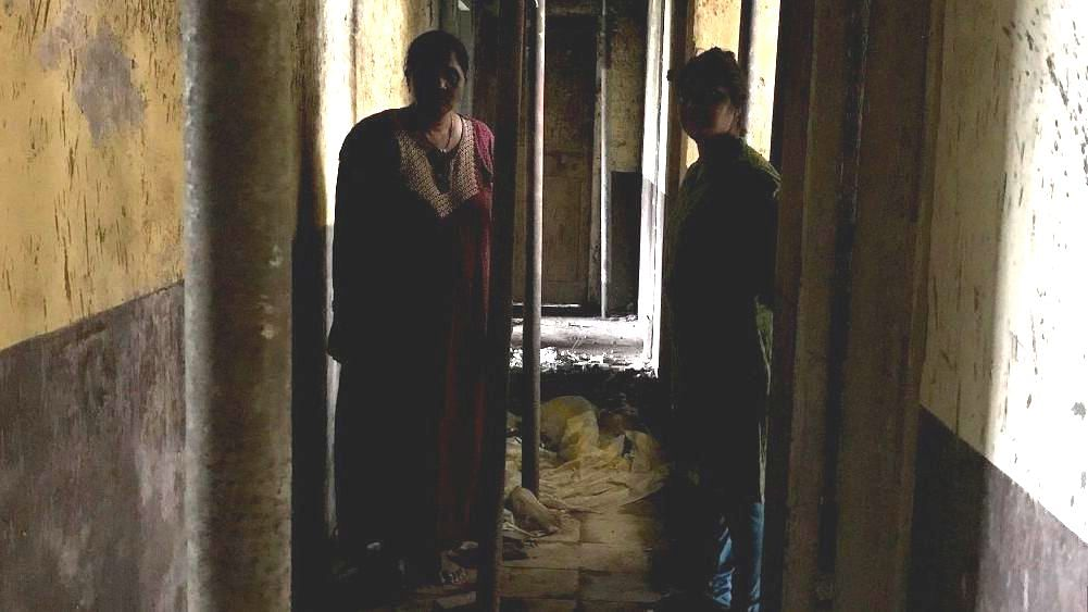 Sunita Lokhande* and Sudha Kamble* stand in the corridor one floor above their flats in the Saki Naka police housing complex. Three buildings in the complex have been declared unsafe by the PWD.