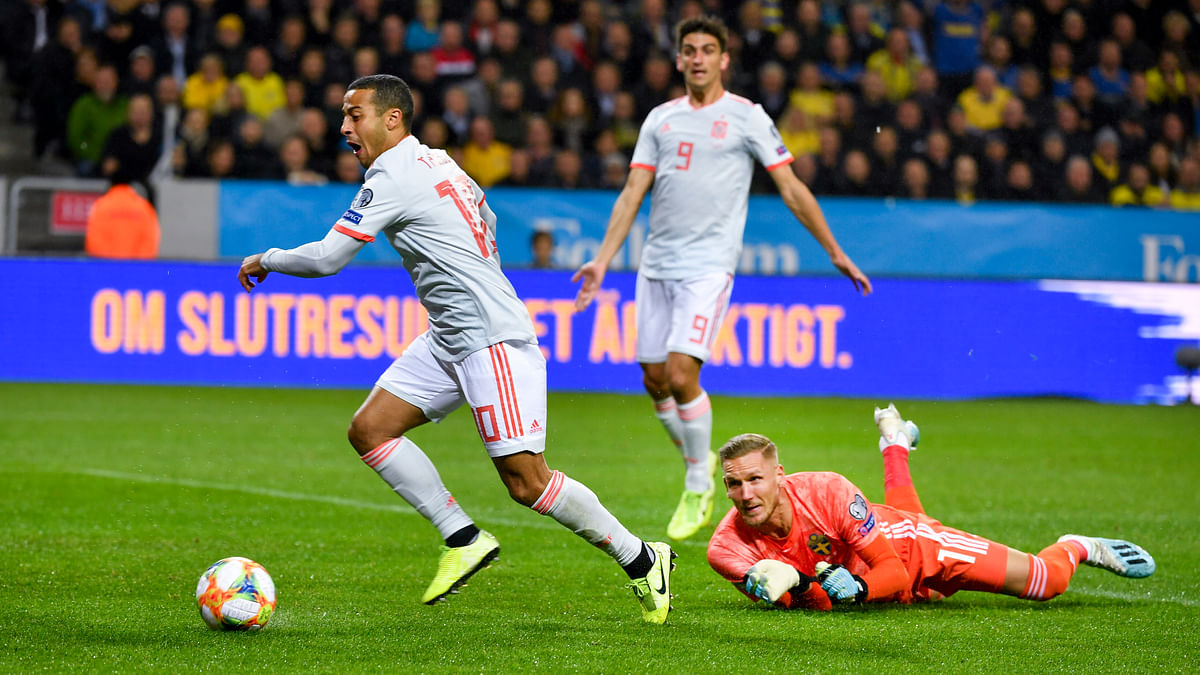 Spain's Thiago Alcantara (L) dribbles the ball past Sweden's goalkeeper Robin Olsen during the Euro 2020 Group F qualification soccer match between Sweden and Spain at Friends Arena in Solna, Stockholm, Sweden, on Oct. 15, 2019.