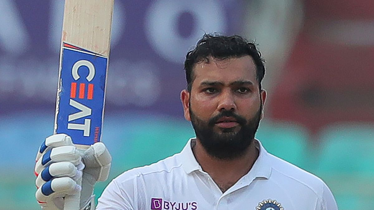India's Rohit Sharma raises his bat after scoring a century during the fourth day of the first cricket test match against South Africa in Visakhapatnam, India, Saturday, Oct. 5, 2019.