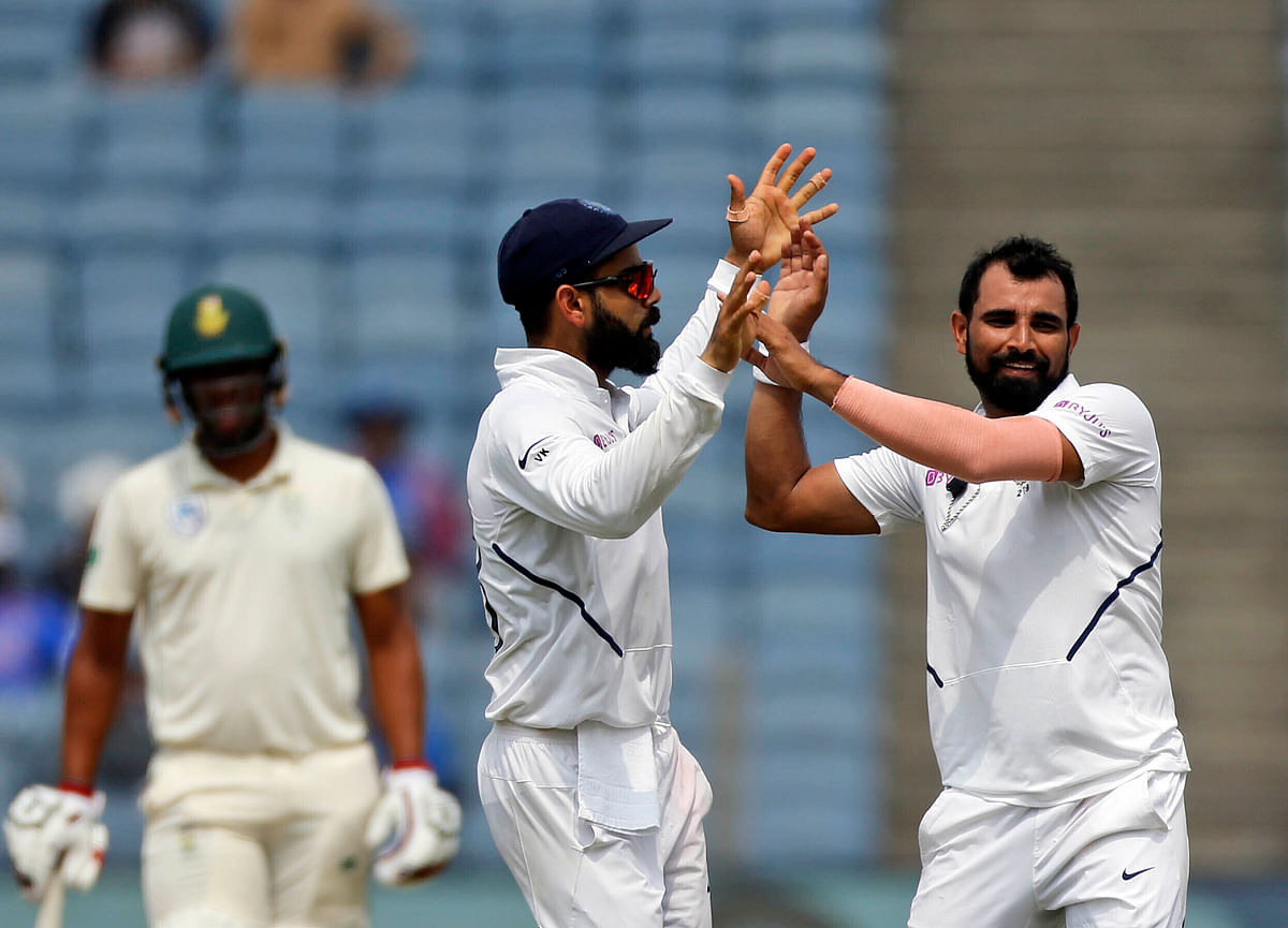 Mohd Shami and Virat Kohli during the second Test between India and South Africa at Pune.