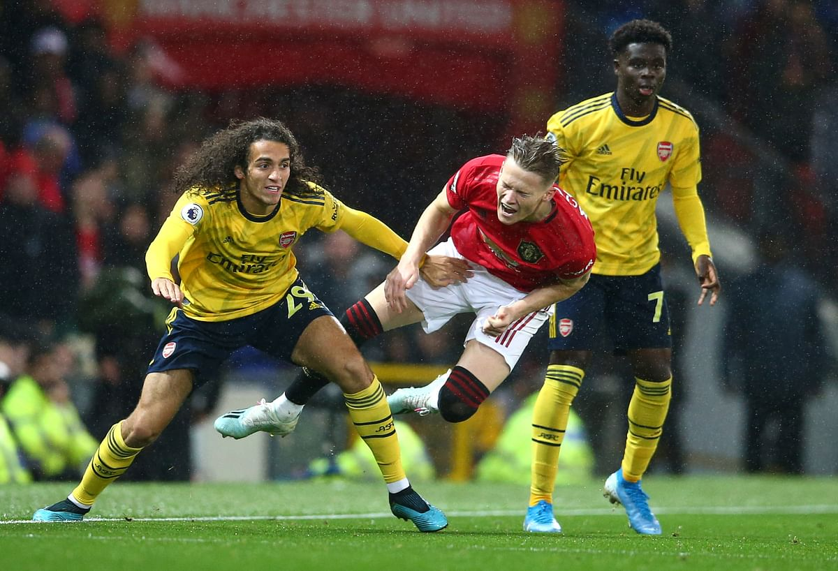 Manchester United's Scott McTominay, centre, vies for the ball with Arsenal's Matteo Guendouzi, left, during the English Premier League soccer match.