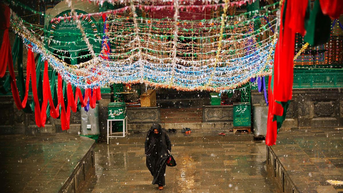 A Kashmiri Muslim woman walks outside a Muslim shrine as it rains in Srinagar. (Image used for representational purposes.)