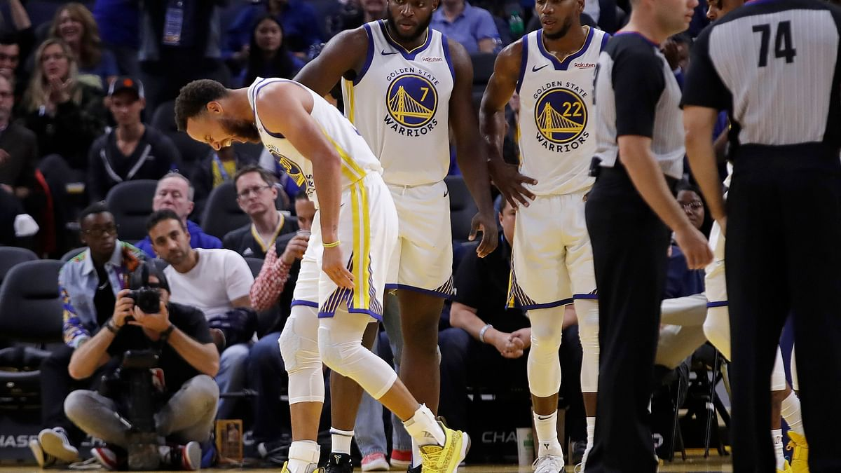 Golden State Warriors' Stephen Curry, left, grimaces in pain after Phoenix Suns' Aron Baynes fell on him during the second half of an NBA basketball game Wednesday, Oct. 30, 2019, in San Francisco.