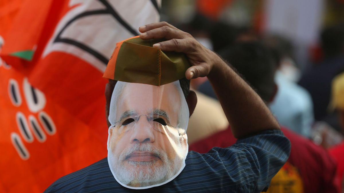 A supporter of Bharatiya Janata Party wearing a mask of Prime Minister Narendra Modi participates in an election campaign rally in Mumbai, India.