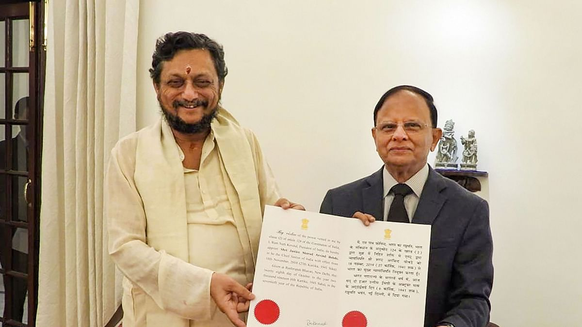 Justice SA Bobde (left) is being present the warrant of appointment to Chief Justice of India-designate by Principal Secretary to PM, PK Mishra.