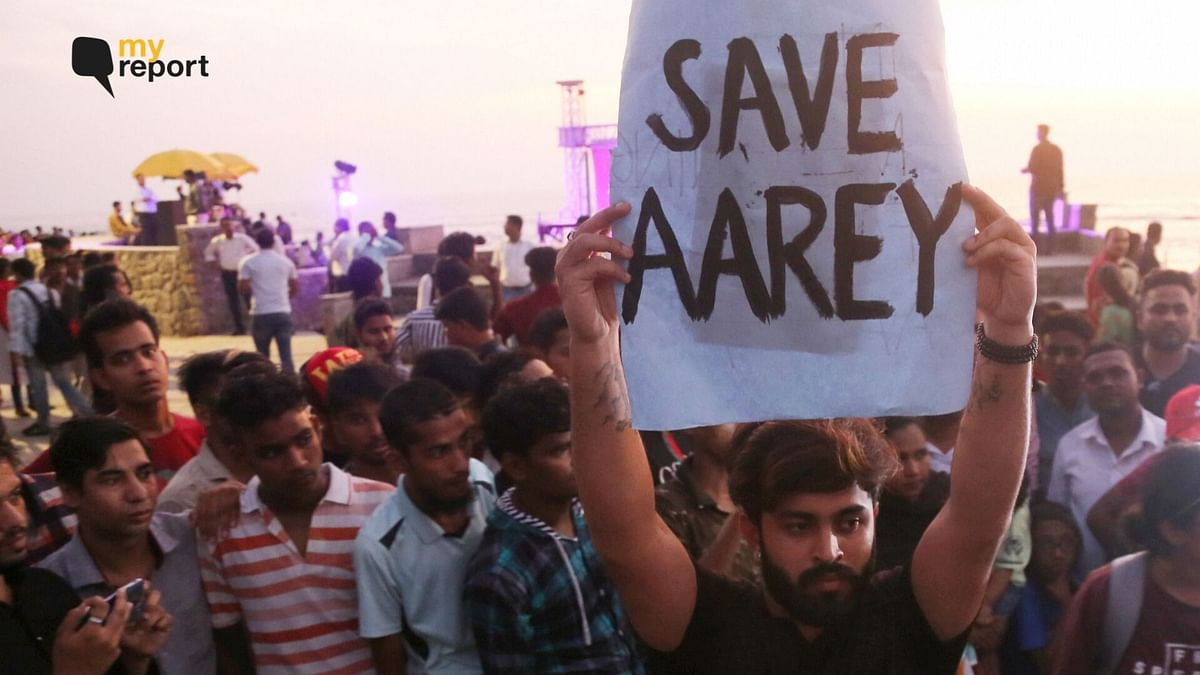 An activist holds a placard during a protest against cutting down of trees at Mumbai's Aarey Colony.