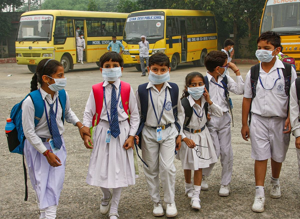 Students wearing mask walk amid an atmoshphere shrouded in smog in Rohtak, Saturday, 2 November 2019.