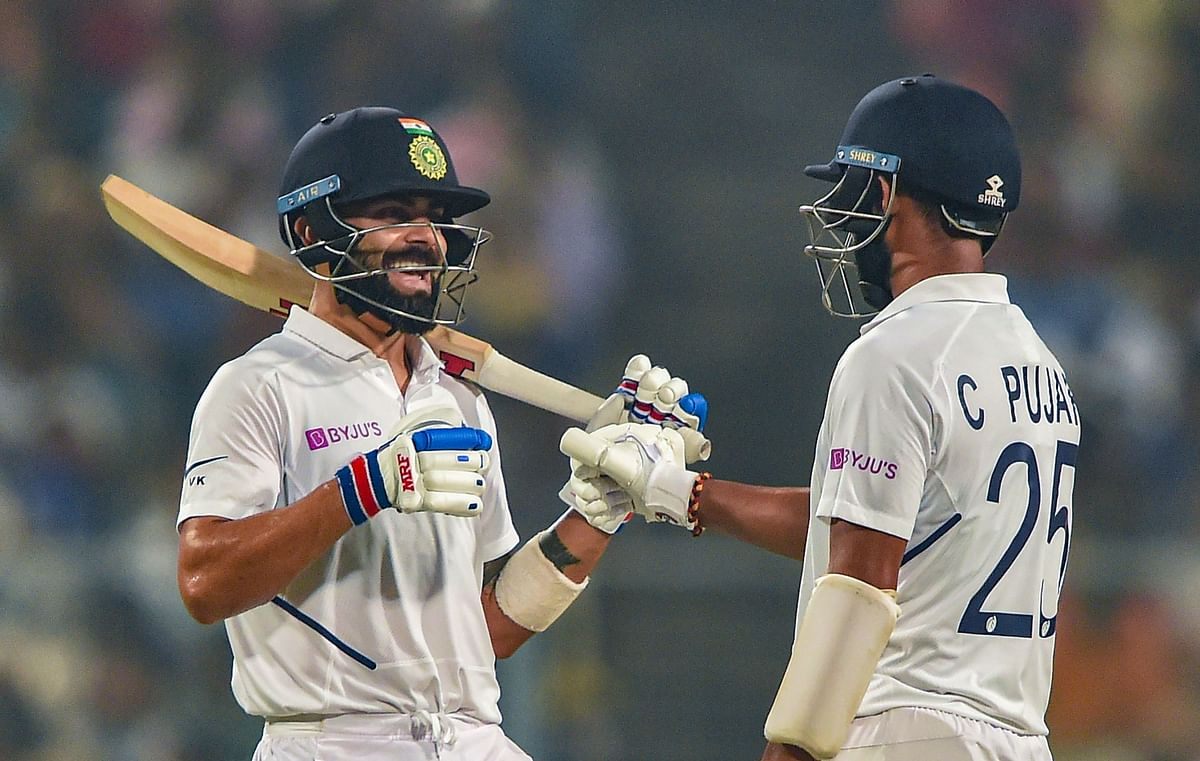 Indian Skipper Virat Kohli and teammate Cheteswar Pujara celebrate their partnership on Day 1 of the 1st pink-ball day-night cricket Test match between India and Bangladesh, at Eden Gardens in Kolkata.