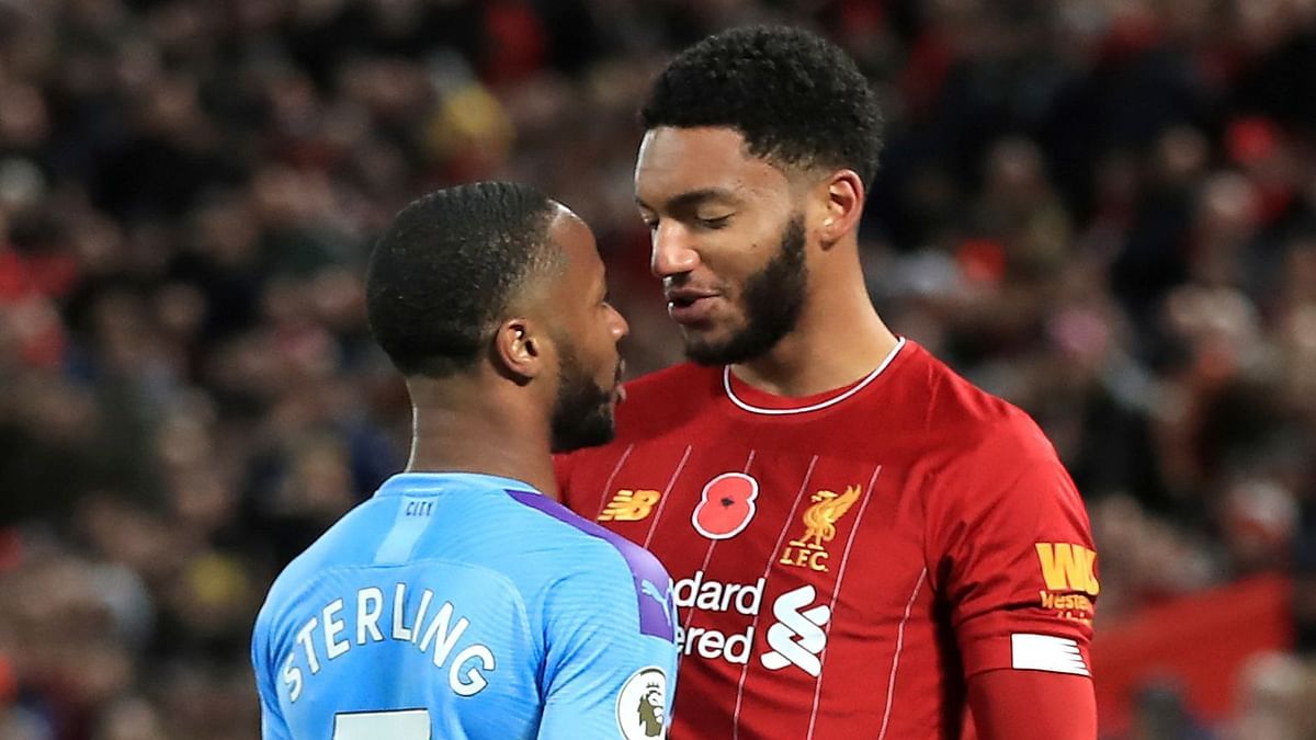 Liverpool's Joe Gomez, right, and Manchester City's Raheem Sterling clash during the Premier League soccer match at Anfield, Liverpool.