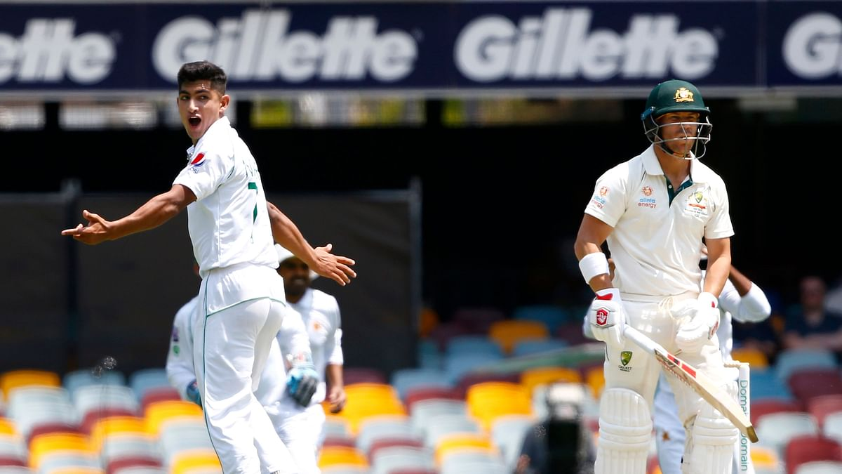 Pakistan's Naseem Shah, left, celebrates the wicket of Australia's David Warner, right with bat, before the decision was overturned due to a no ball called during their cricket test match in Brisbane, Australia, Friday, Nov. 22, 2019.