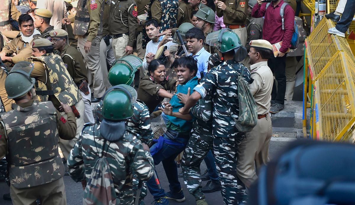 Police attempt to stop a JNU student from crossing the barricades during a protest march towards Parliament, on the first day of the Winter Session, in New Delhi, Monday, 18 November 2019.