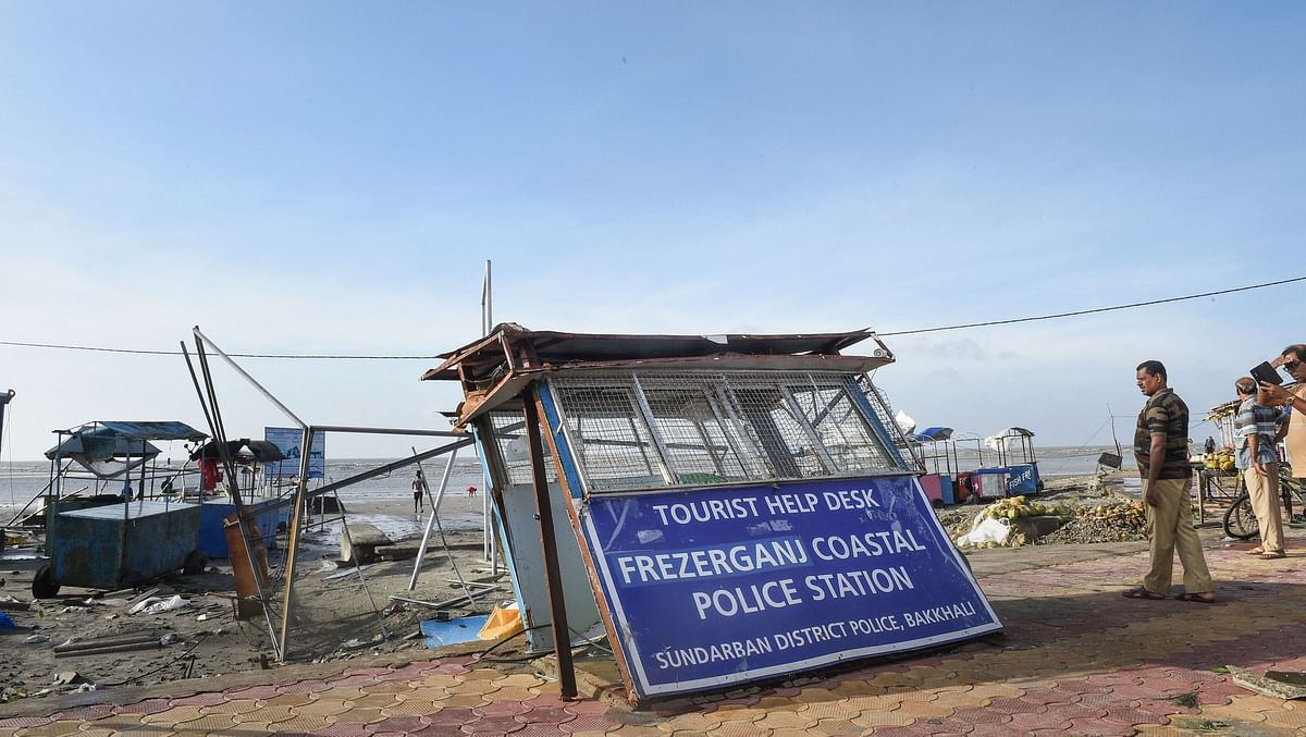 A policeman stands next to damaged Fraserganj Coastal Police Station along a beach in the aftermath of the cyclone.