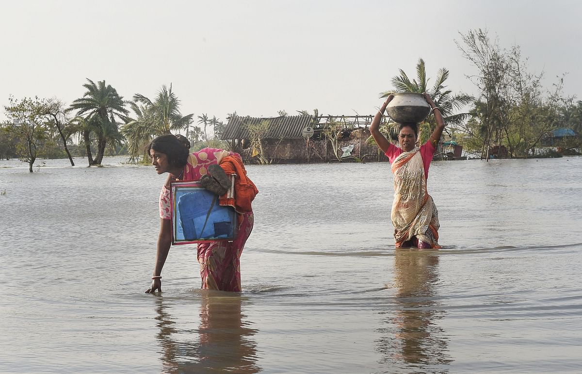 Villagers make through a flooded area following cyclone Bulbul at Bakkhali on Sunday.