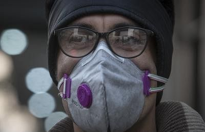 TEHRAN, Nov. 15, 2019 (Xinhua) -- A man wearing a mask waits at a bus station in Tehran, Iran, on Nov. 14, 2019. The Iranian authorities closed kindergartens and primary schools on Wednesday over serious air pollution in Iran