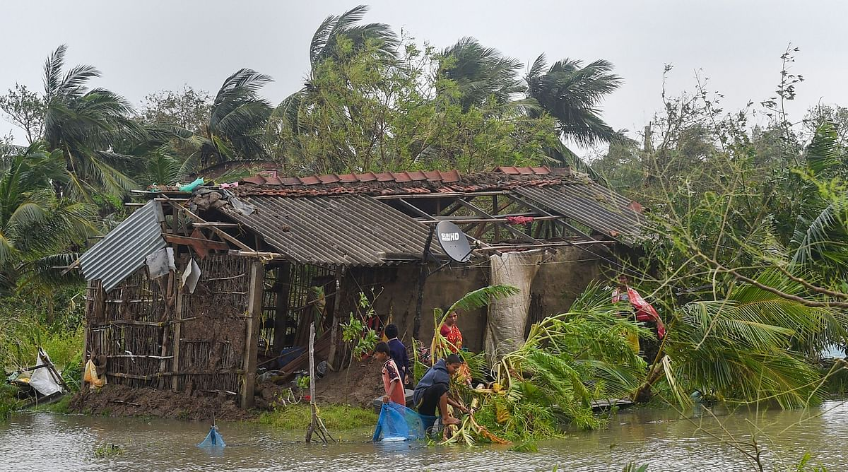 Villagers collect their belongings from the remnants of their house in the aftermath of the cylcone in Bakkhali.