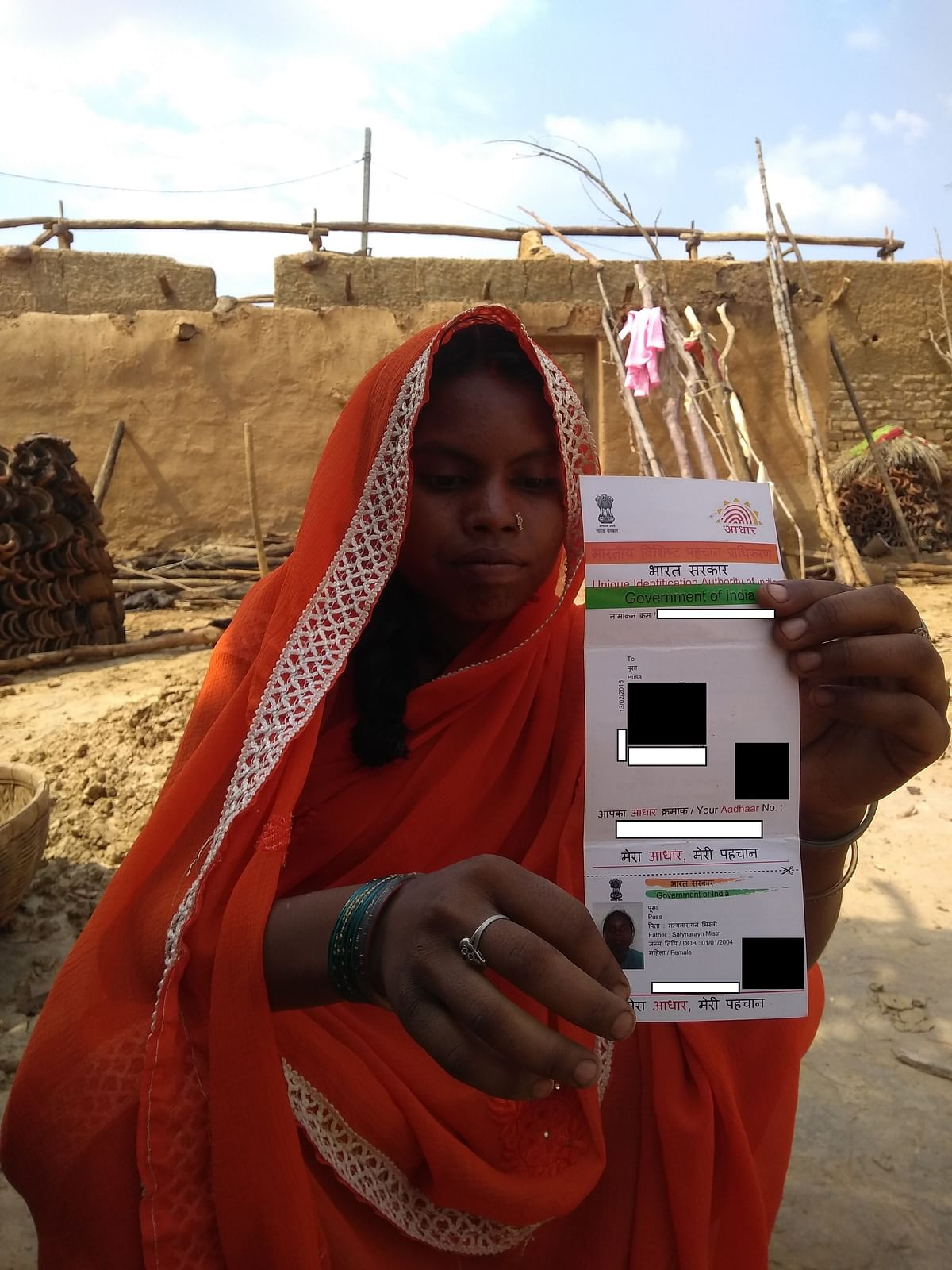 Usha Devi holding her Aadhaar card in which her name has been mistakenly mentioned as 'Pusa'.