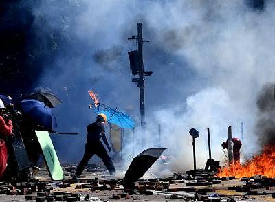 HONG KONG, Nov. 27, 2019 (Xinhua) -- A rioter sets fire and destroys public facilities outside the Hong Kong Polytechnic University in south China