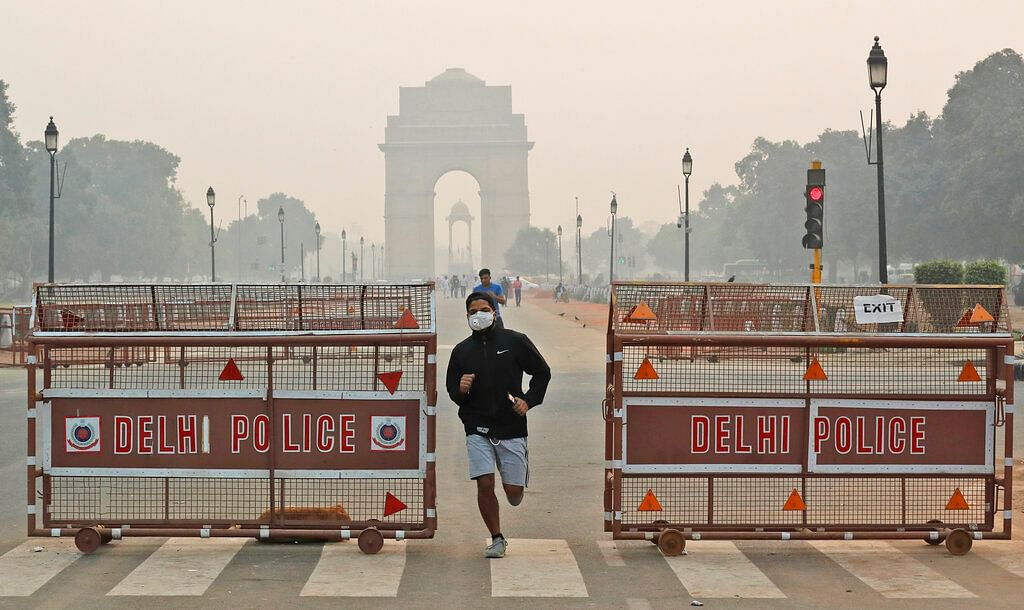 A jogger wears a pollution mask early morning amidst light smog in New Delhi. The national capital's air quality dropped to the season's worst on the morning after Diwali.