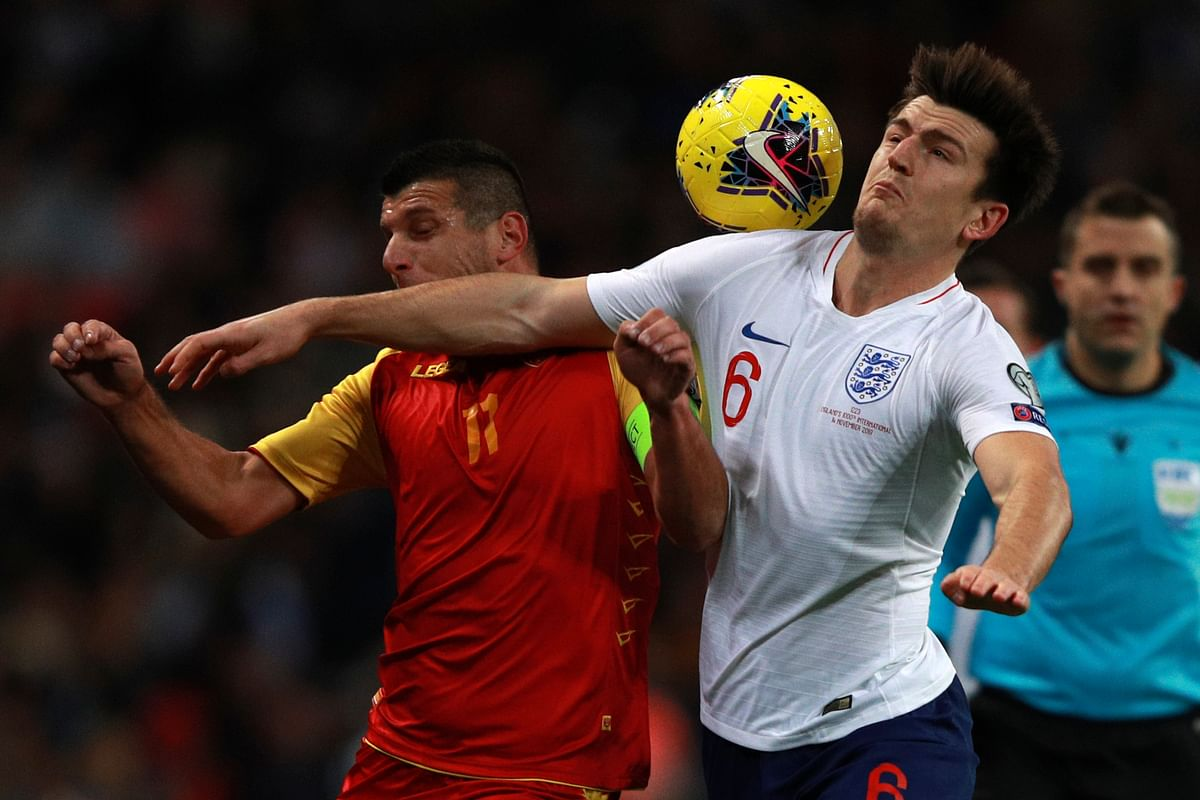 England's Harry Maguire, right, and Montenegro's Fatos Beciraj fight for the ball during the Euro 2020 group A qualifying football match between England and Montenegro at Wembley stadium in London.