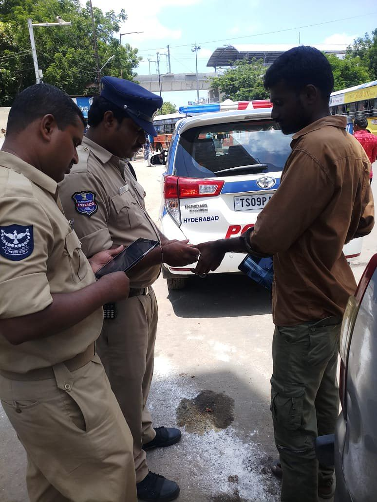 Police personnel taking biometrics of people to compare with the database of known criminals.