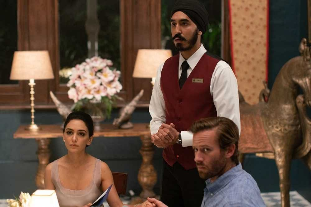 Dev Patel as a staff member with Armie Hammer and Nazanin Boniadi as guests in <i>Hotel Mumbai</i>.