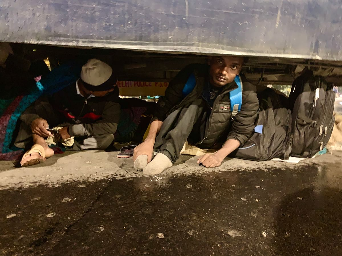 Differently-abled protesters hide from the rain underneath a bus.