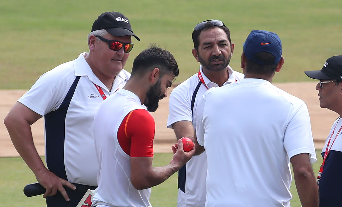 India's captain Virat Kohli, second left, checks out the new pink ball as he interacts with umpires.