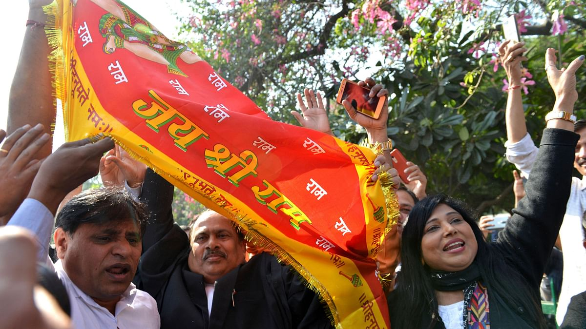 People wave a flag that reads 'Glory to lord Rama' as they celebrate the verdict outside the Supreme Court in New Delhi, on Saturday, 9 November.