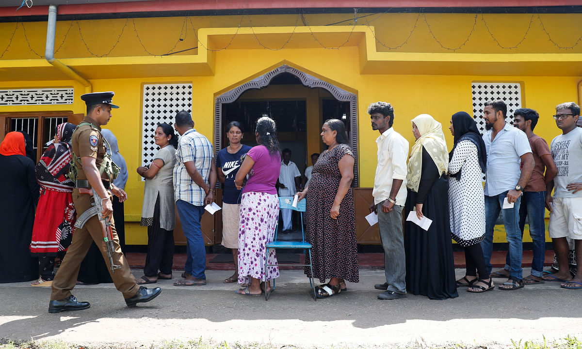 Sri Lankans queue to cast their votes as a police officer stands guard at a polling station during the presidential election in Colombo, Sri Lanka, Saturday, 16 November 2019. Polls opened in Sri Lanka's presidential election Saturday after weeks of campaigning that largely focused on national security and religious extremism in the backdrop of the deadly Islamic State-inspired suicide bomb attacks on Easter Sunday.