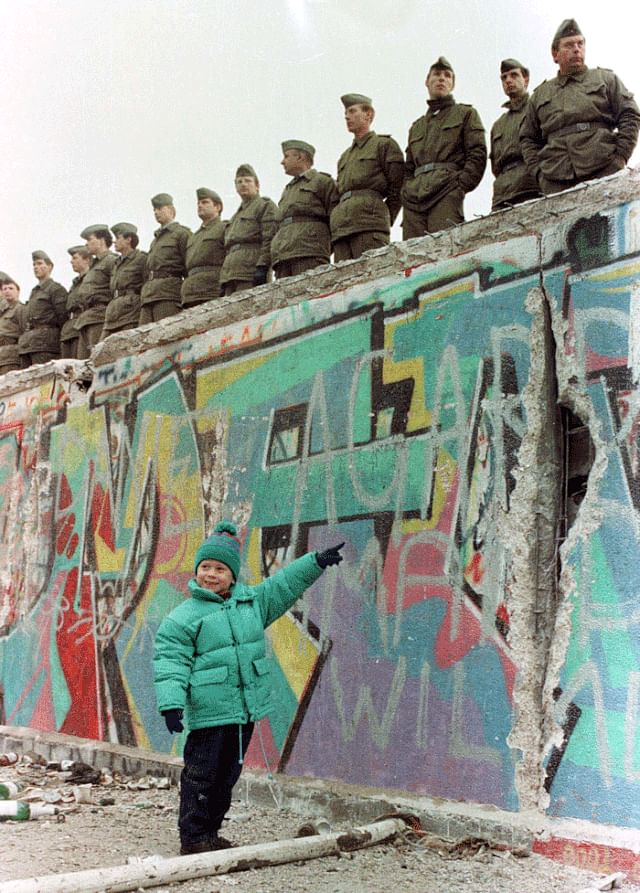 A West German girl points to a hole in the Berlin Wall, as guards stand on watch.