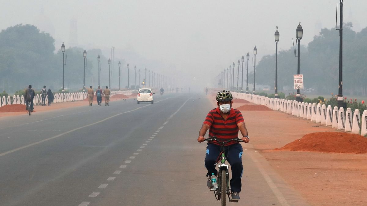 A man cycles wearing a pollution mask early morning amidst light smog in New Delhi.