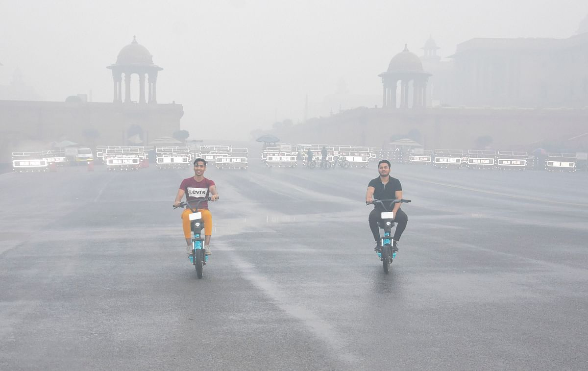 Commuters ride on Rajpath amid heavy smog in New Delhi on Sunday.