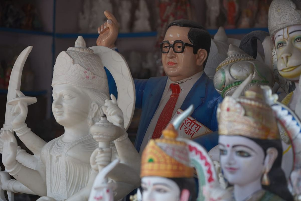 A statue of BR Ambedkar stands amidst the statues of gods and goddesses in the shop.