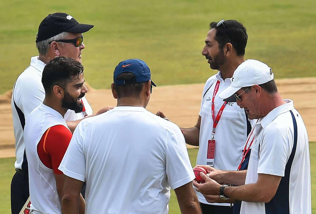 Umpires check out the new pink ball as India's captain Virat Kohli,  watches after batting in the nets during a training session ahead of their first cricket test match against Bangladesh in Indore.