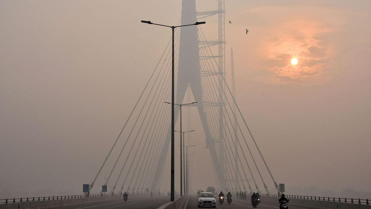 The sun is vaguely seen behind the Signature Bridge amid heavy smog, in New Delhi.