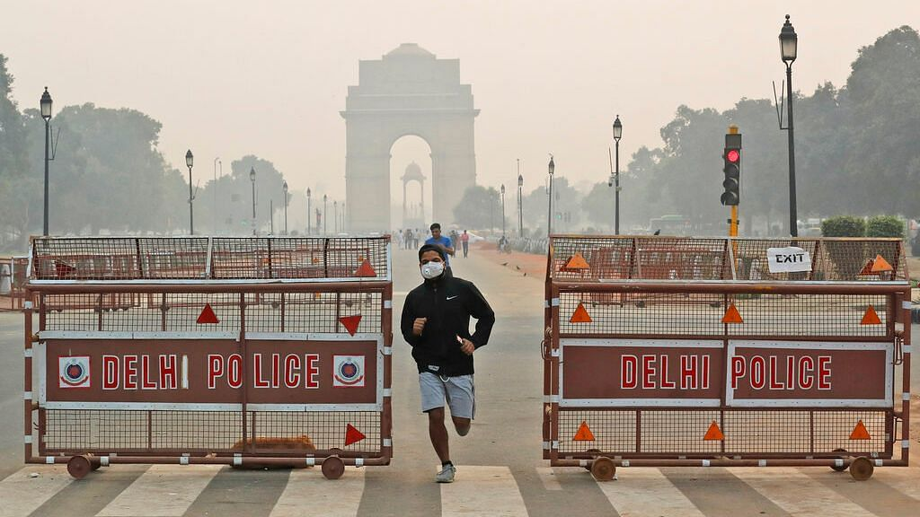 A jogger wears a pollution mask early morning amidst light smog in New Delhi.