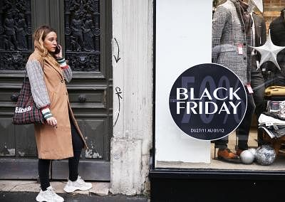 """PARIS, Nov. 28, 2019 (Xinhua) -- A woman makes a phone call beside a """"Black Friday"""" poster in Paris, France, Nov. 27, 2019. Some shops in Paris started sales promotion recently ahead of the upcoming """"Black Friday"""" that falls on Nov. 29. (Xinhua/Gao Jing/IANS)"""