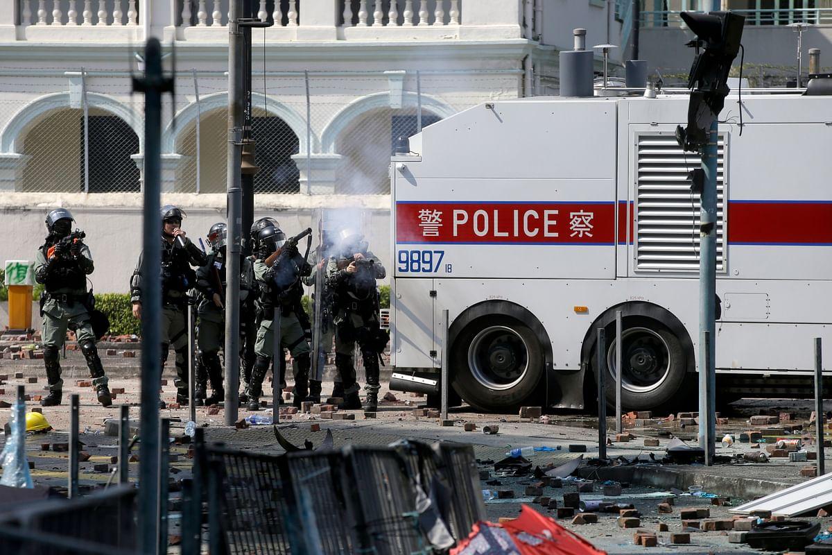 Policemen in riot gear fire teargas outside Hong Kong Polytechnic University in Hong Kong on Monday, 18 November.