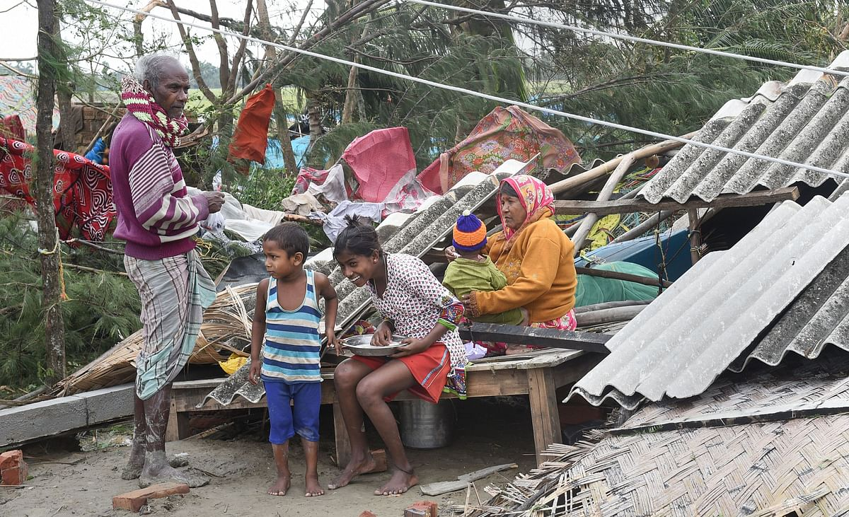 Bakkhali: A family sits amongst the rubble of their house on Sunday.