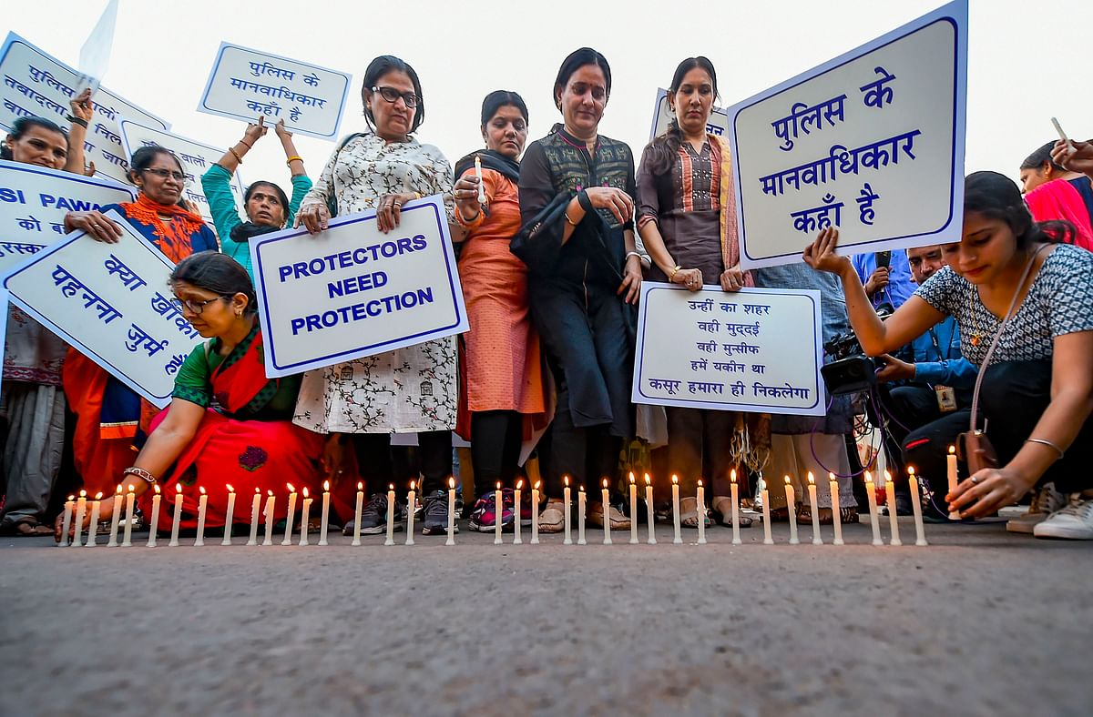 Families of police personnel take part in a candle-light protest over the alleged repeated incidents of violence against the police by lawyers, at India Gate in New Delhi, Tuesday.