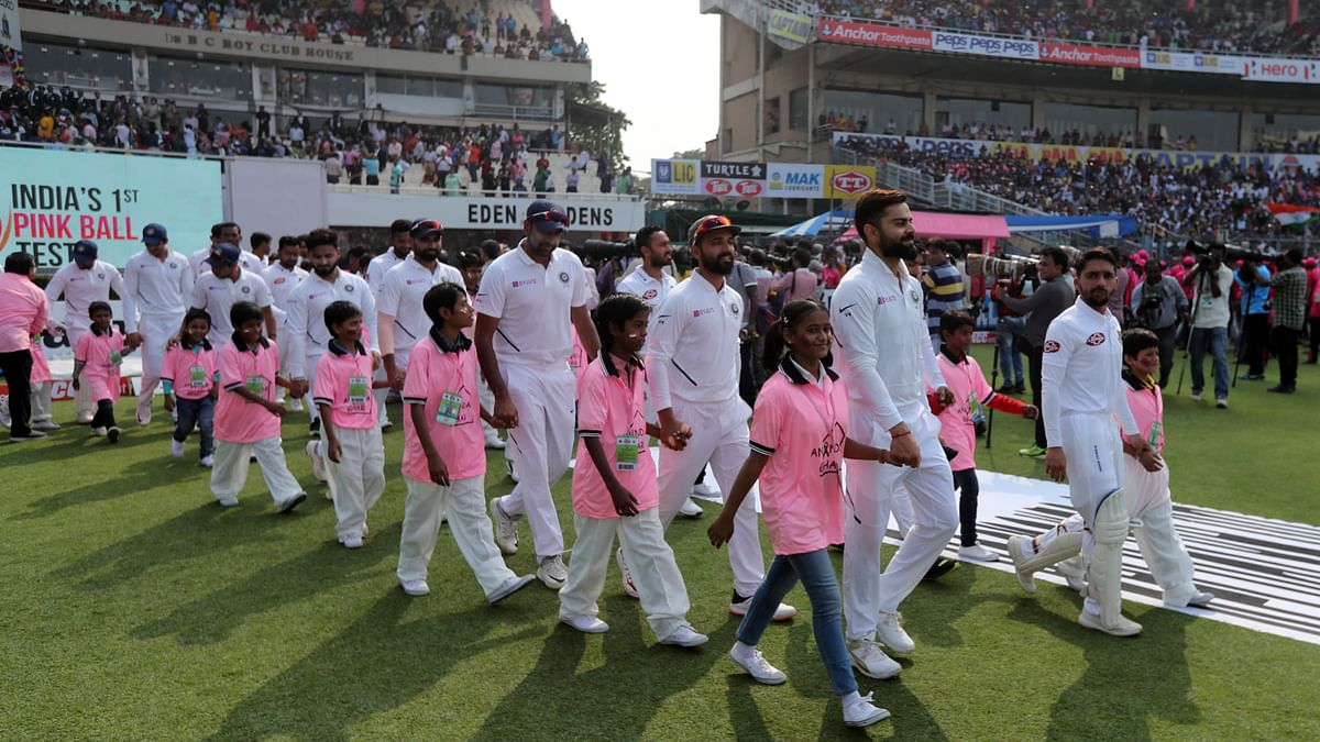 Virat Kohli of India and Mominul Haque of Bangladesh come out with their teams on Day 1 of the Pink Ball Test at the Eden Gardens in Kolkata.