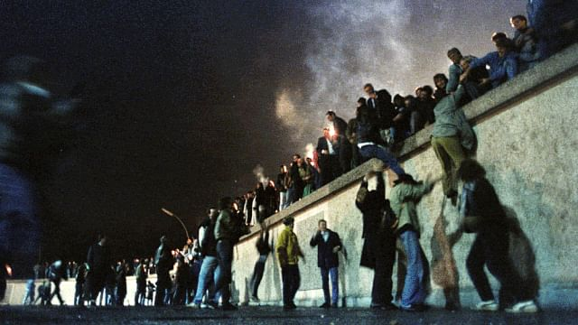 East Germans climb the Berlin Wall after it was opened in November 1989.