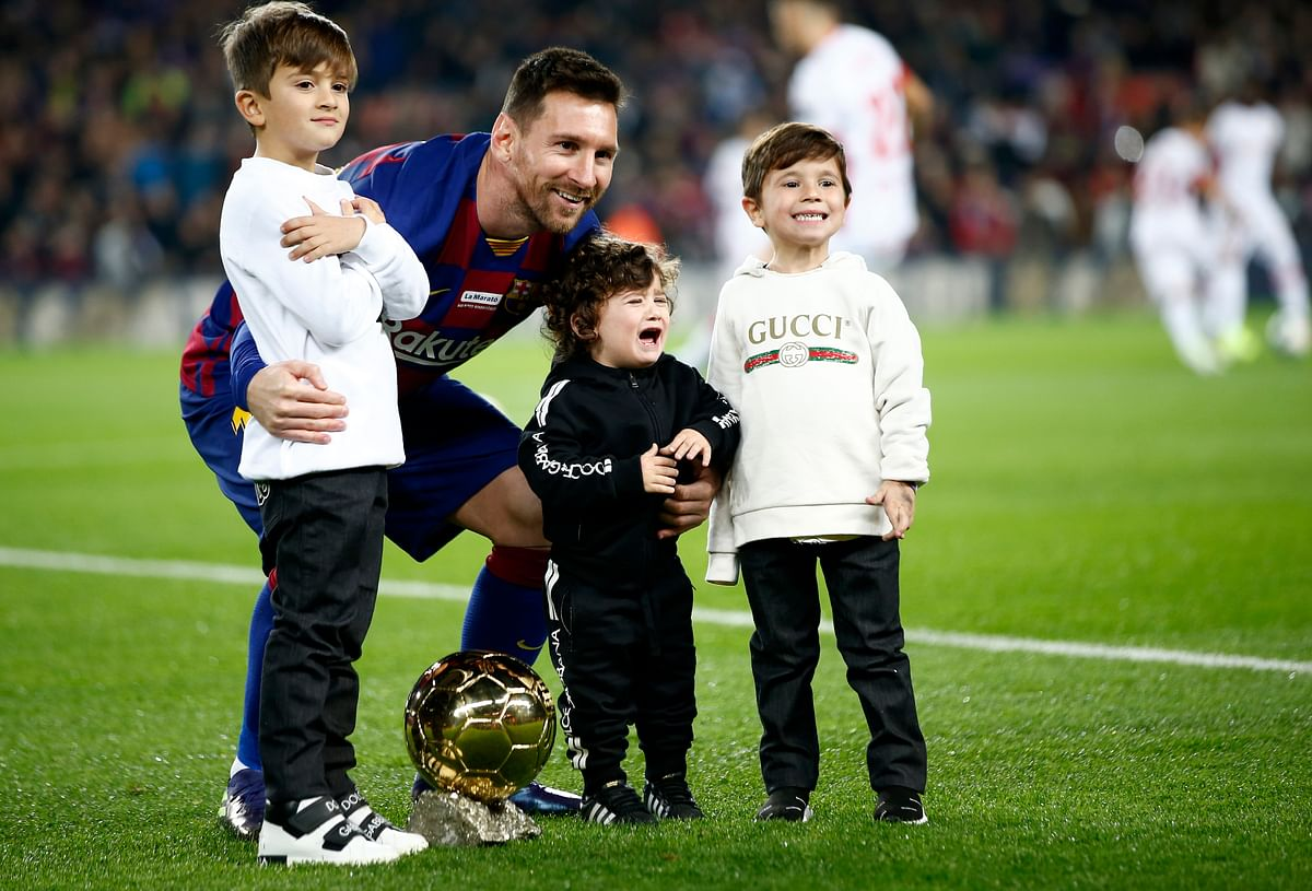 Barcelona's Lionel Messi, with his children, poses with his sixth Golden Ball for the best player of the year that he was awarded earlier in the week, before a Spanish La Liga soccer match between Barcelona and Mallorca at Camp Nou stadium.