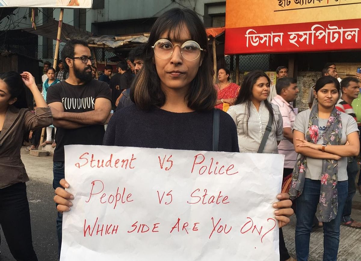 A protester outside Jadavpur University holds up a placard referencing Sunday's violence in Jamia Millia Islamia.